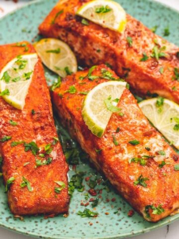 3 Salmon Fillets on green plate topped with limes.