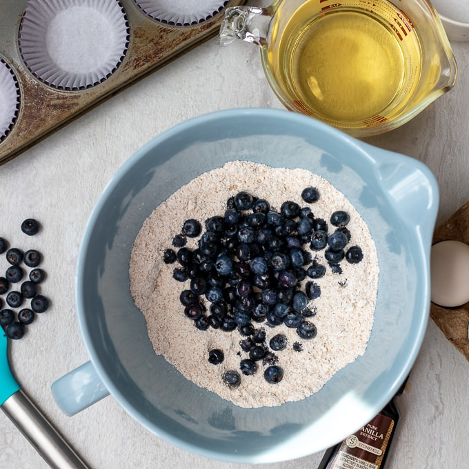 Blueberries mixed into flour in blue mixing bowl