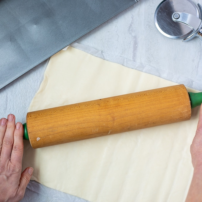 Puff Pastry Being rolled out with wooden rolling pin