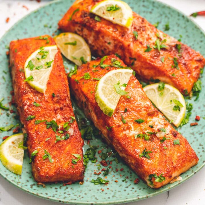 3 Salmon Fillets on green plate topped with limes
