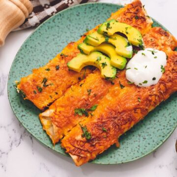 Chicken Enchiladas on plate topped with avocado