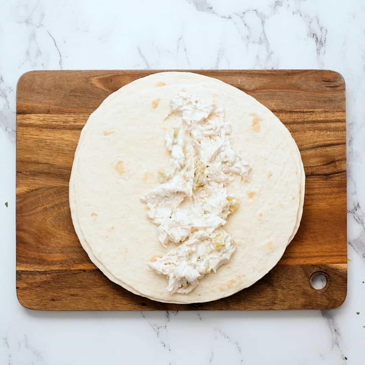 Chicken mixture on flour tortilla.