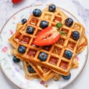 Whole Wheat waffles on plate with berries and syrup