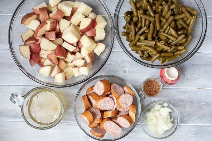 Red potatoes, green beans, smoked sausage, cajun seasoning, and chicken stock on white counter