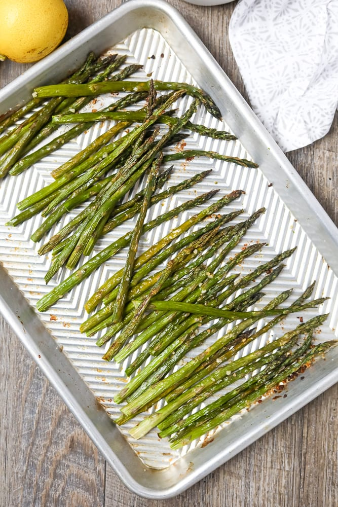 Asparagus tossed with lemon and olive oil on roasting pan