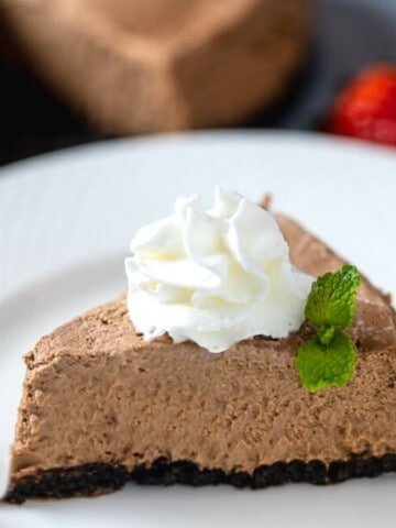 Slice of Instant Pot Chocolate Cheesecake topped with whipped cream.