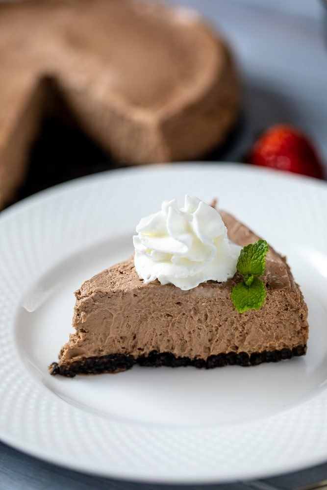 Slice of Instant Pot Chocolate Cheesecake topped with whipped cream