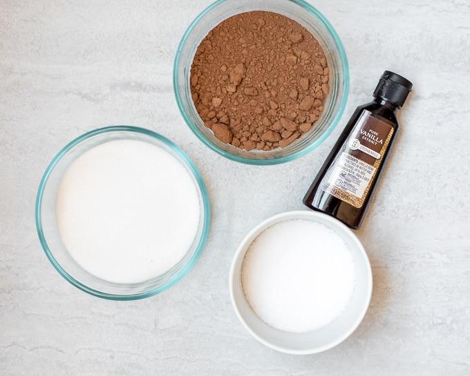 sugar, cocoa powder, vanilla and salt on white counter