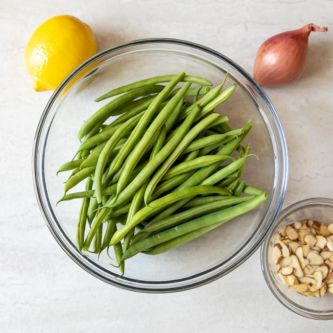 fresh green beans, lemon, shallot and almonds on white counter