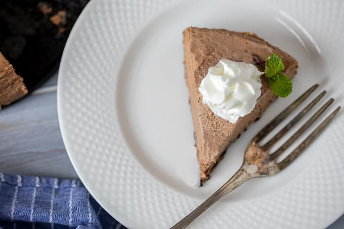 Slice of Chocolate Cheesecake on white plate with a dollop of whipped cream.