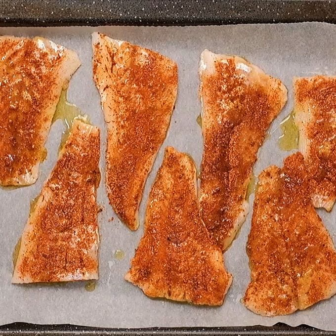 Seasoned cod fillets on baking sheet