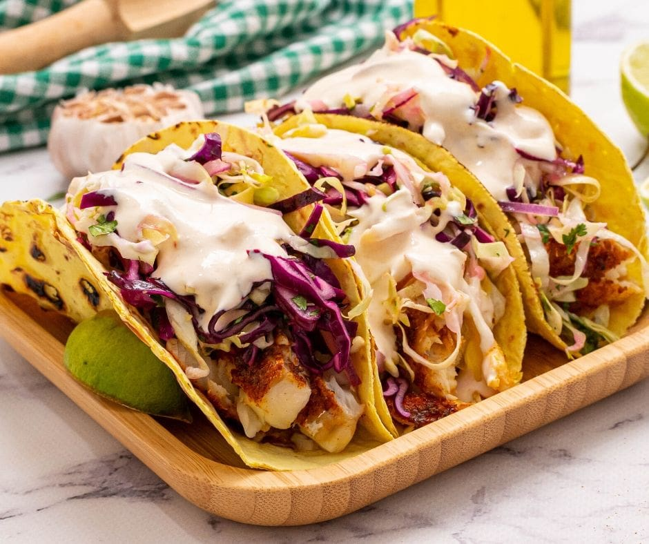 Fish Tacos with slaw and mayo sauce on wooden platter