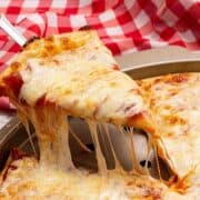 Slice of cheese pizza being pulled out of pizza pan