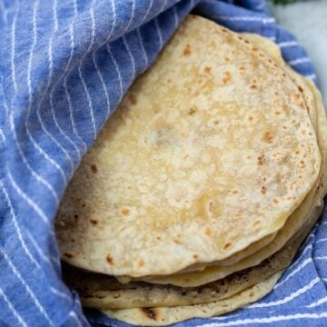 Stack of homemade tortillas in blue towel