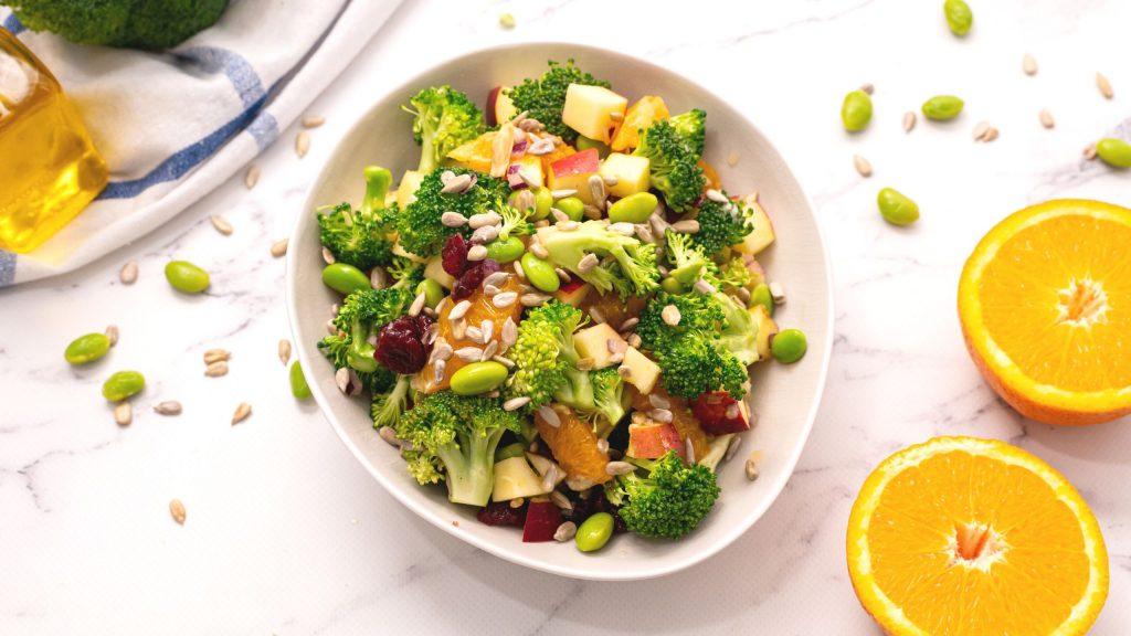 Bowl of Healthy Broccoli Salad next to fresh oranges.