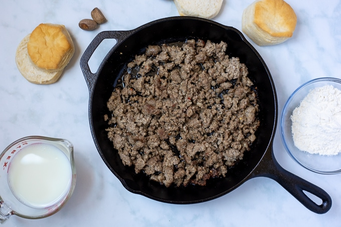 Skillet with browned sausage next to biscuits, flour, and milk