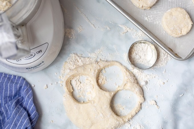 Biscuit dough being cut out using biscuit cutter