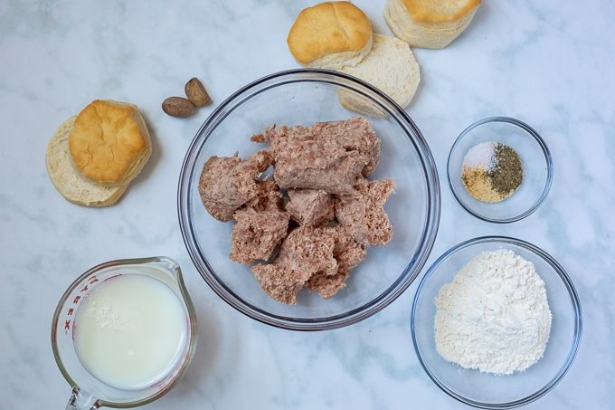 Sausage, biscuits, nutmeg, milk and flour on white counter