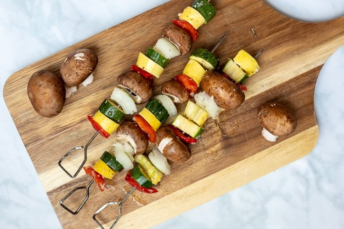Marinated veggies on metal skewers on wooden cutting board ready to be grilled
