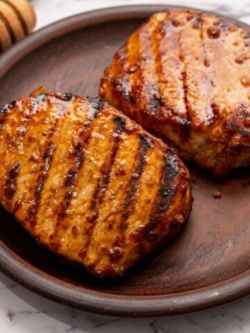 Grilled Pork Chops on wooden platter next to honey.