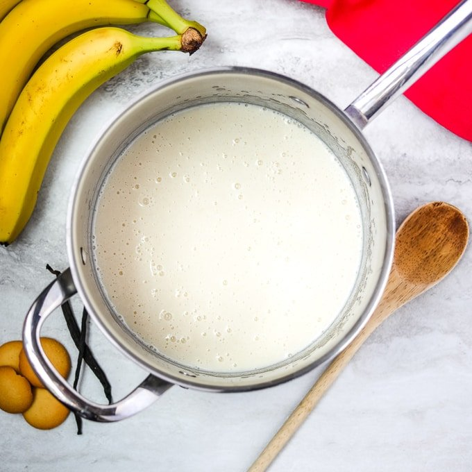 Homemade vanilla custard in silver saucepan next to bananas