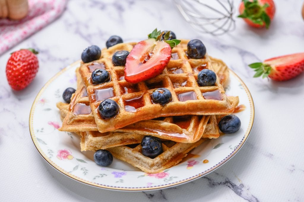 3 waffles on white plate topped with berries and maple syrup