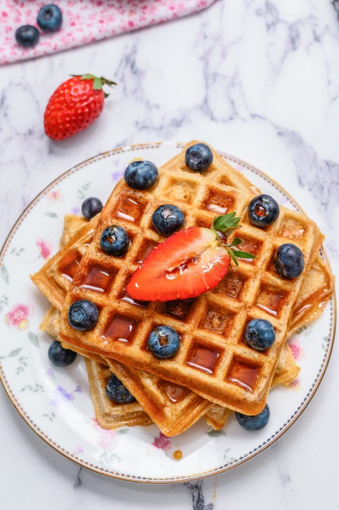 Whole Wheat waffles stacked on plate and topped with berries and maple syrup