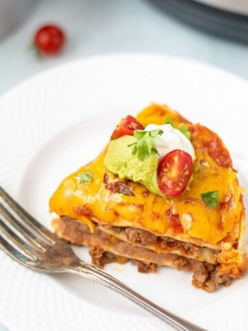 Slice of Instant Pot Mexican Lasagna on white plate with Instant Pot in background