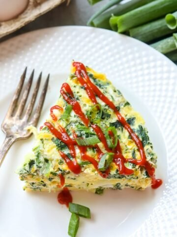 Slice of Spinach Egg Frittata on white plate