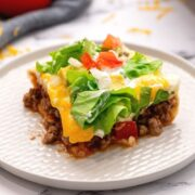 Slice of Mexican Lasagna on white plate topped with tomatoe, onion, and lettuce