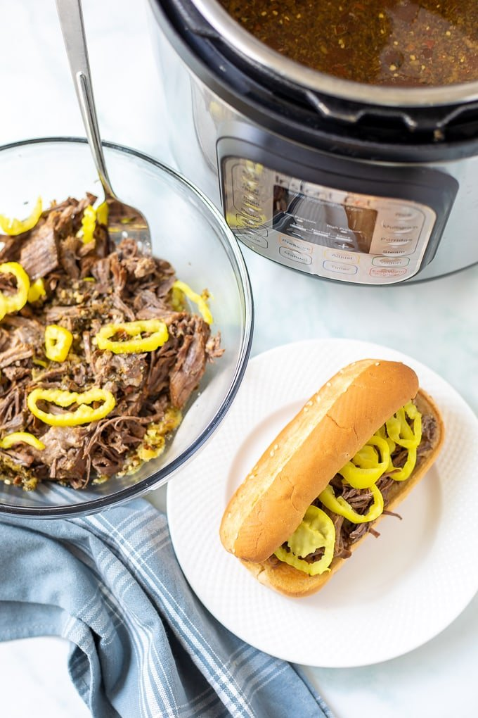 Bowl of Shredded Instant Pot Italian Beef next to Italian Beef Sandwich next to Instant Pot