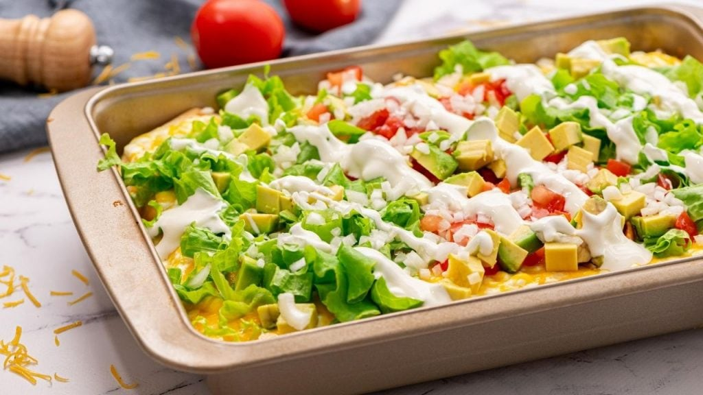 Baked Mexican Lasagna topped with sour cream, tomatoes and lettuce