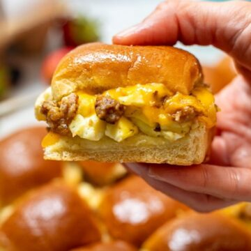 Hand holding breakfast sandwich made with sausage, eggs and cheese