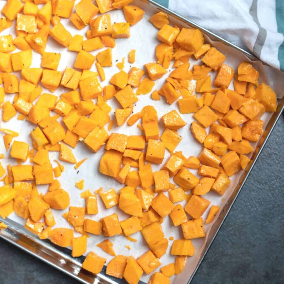 Butternut squash spread out in evenly layer on baking sheet.