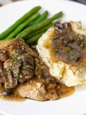 Chicken Marsala on white plate with mashed potatoes and green beans