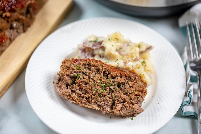 Sliced Meatloaf with mashed potatoes on white plate