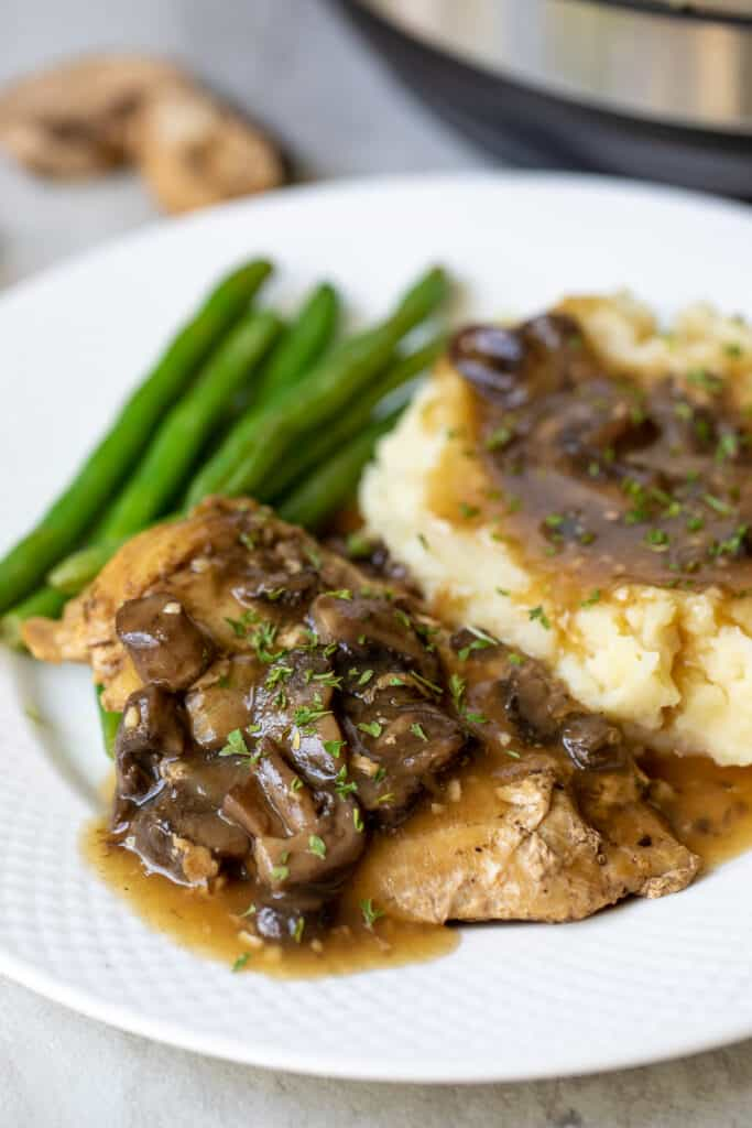 Instant Pot Chicken Marsala on white plate with mashed potatoes and green beans