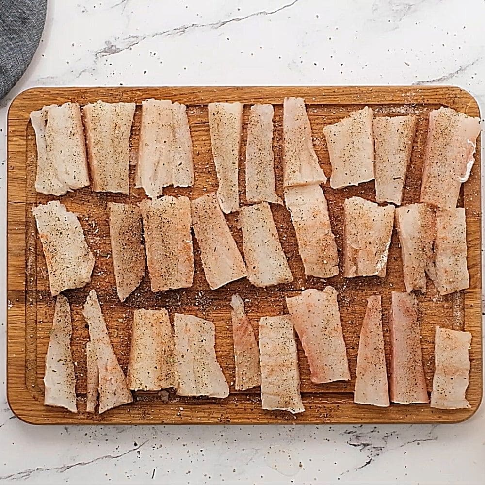 seasoned fish strips on cutting board