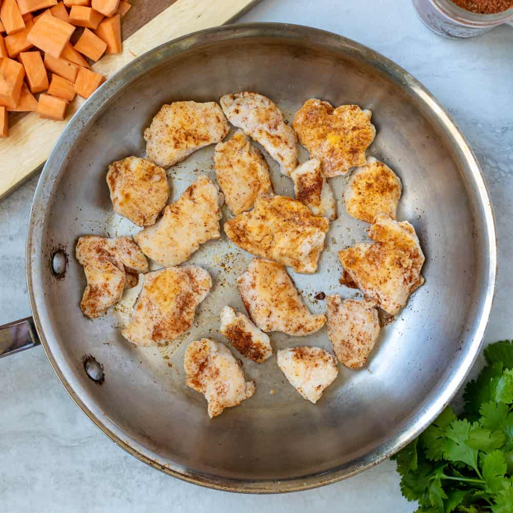 Chicken in skillet with taco seasoning.