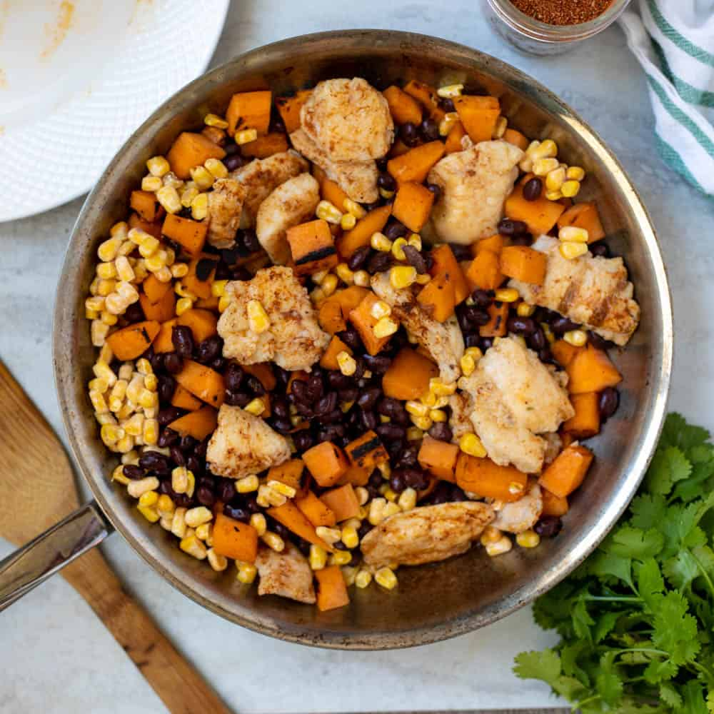 Skillet with sweet potatoes, chicken, corn, and black beans.