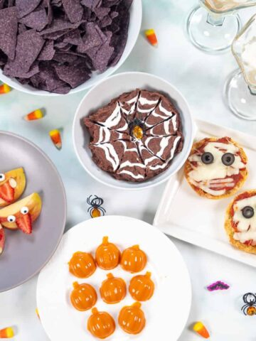 Halloween Snacks for Kids on white counter with halloween decorations.