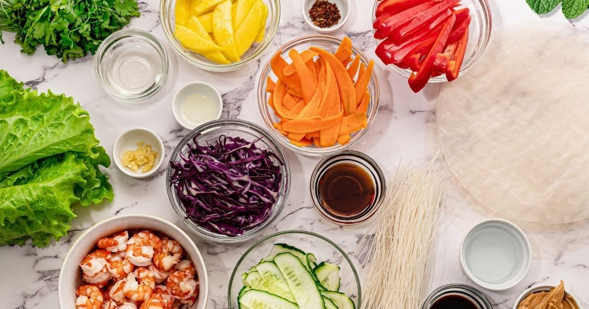 Ingredients for Vietnamese Spring Rolls on white counter.