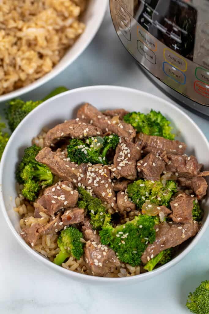 Beef and Broccoli in white dish next to instant pot