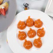 Pumpkin shaped gummies on a white plate.