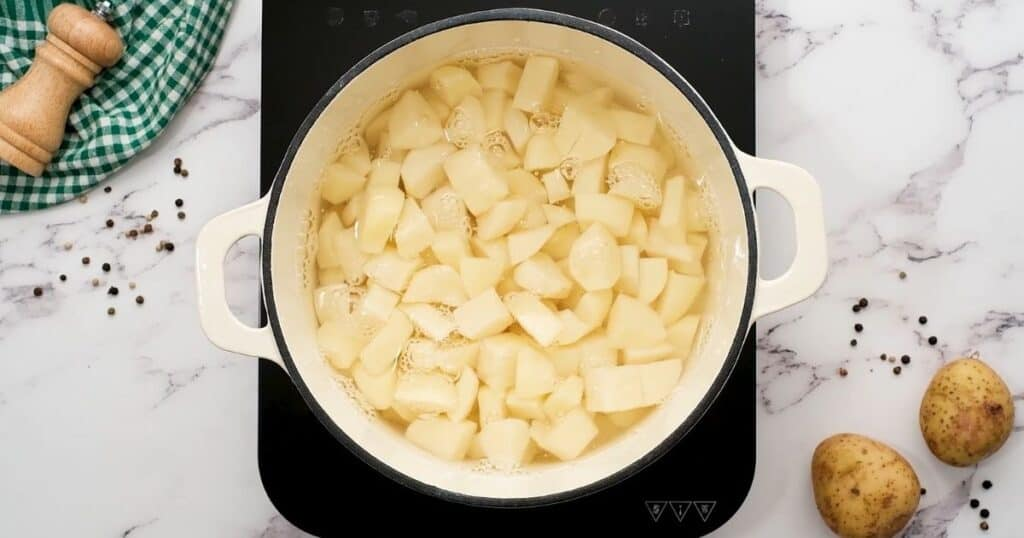 Cubed potatoes in stock pan covered with water.