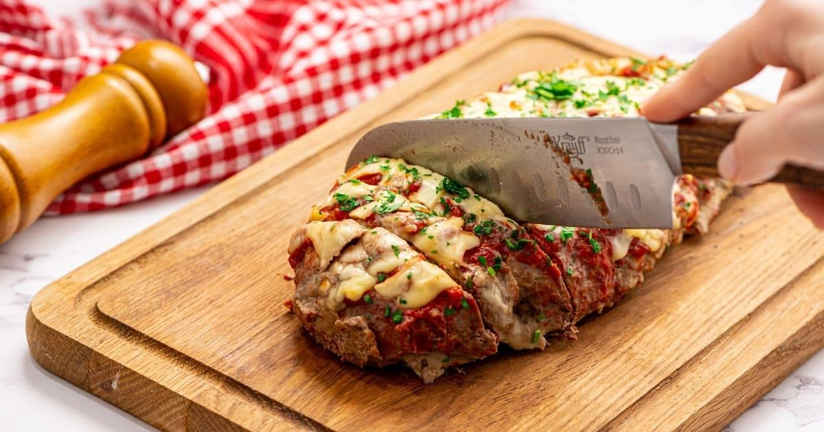 Knife slicing into cheese stuffed meatloaf.