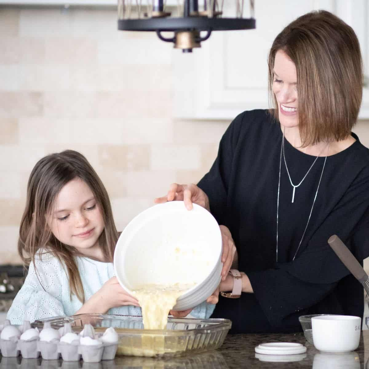 Mom and daughter pouring batter into pan together.