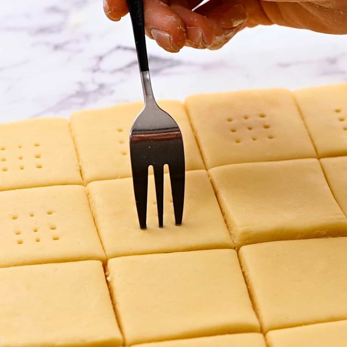 Using a fork to put pricks into shortbread cookie dough.