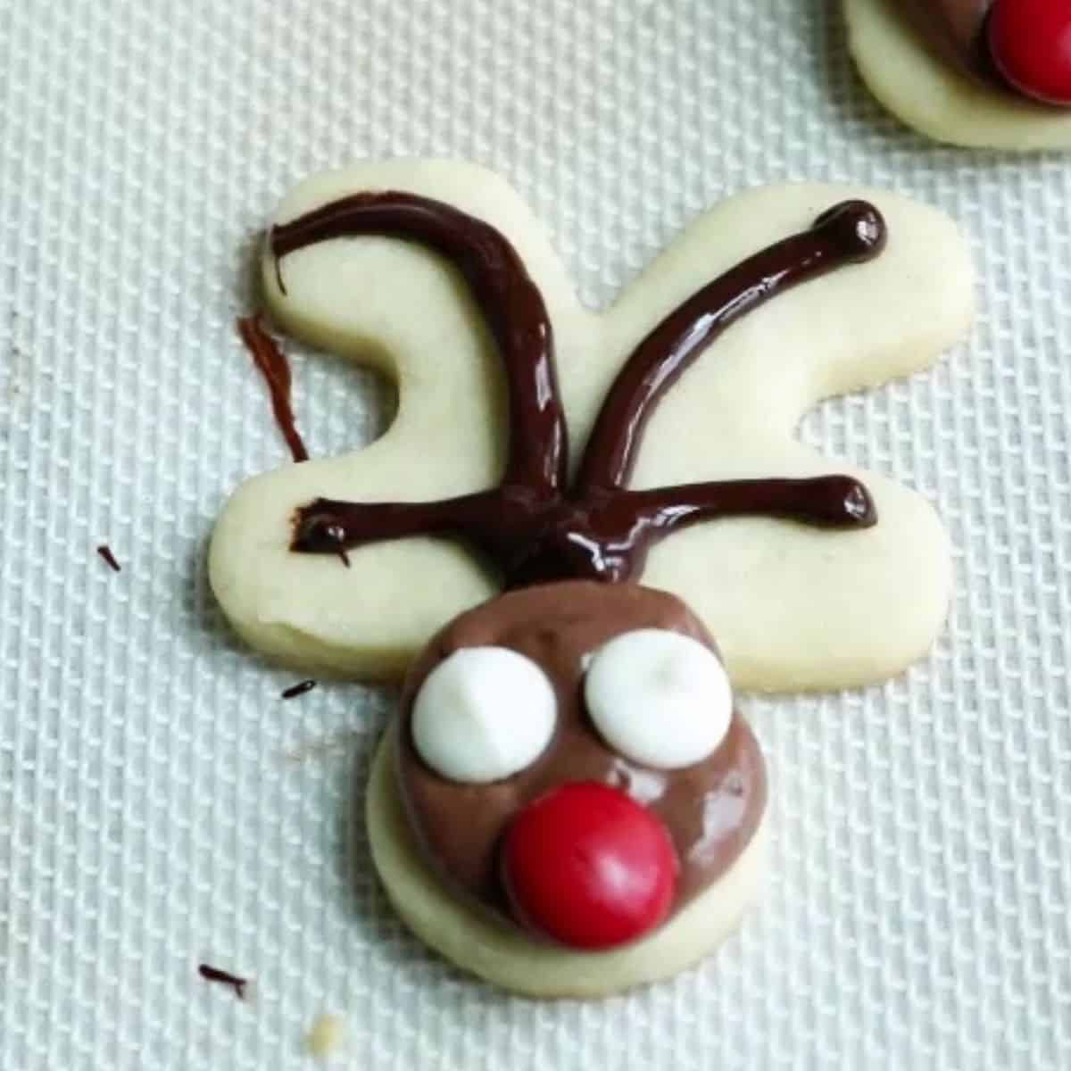 Gingerbread man cookie decorated to look like a reindeer.