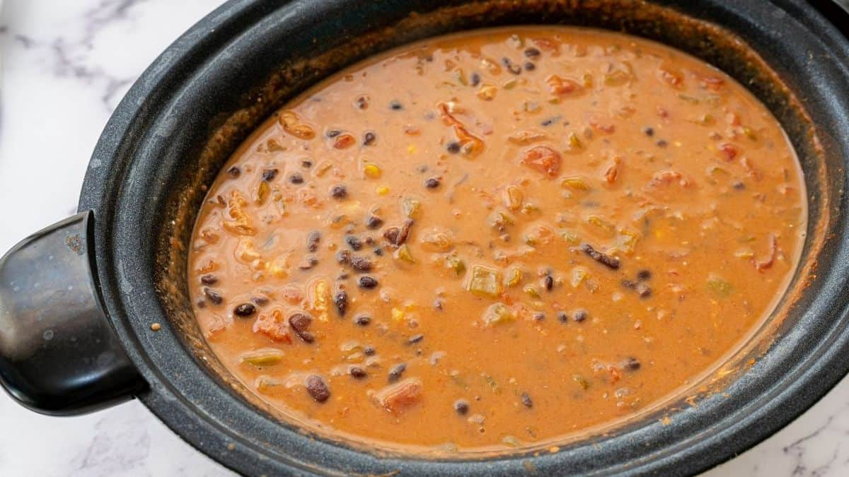 Slow cooker with turkey soup in it.